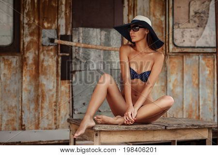 Portrait Of Sexy Beautiful Tanned Woman Posing In Fashion Swimwear Bikini, Hat And Sunglasses At The