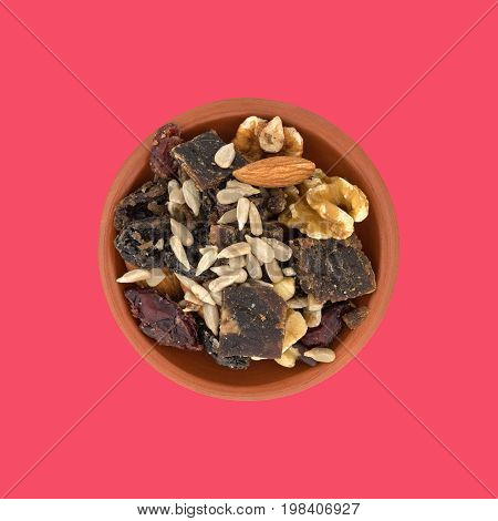 Top view of a serving of beef jerky trail mix in a small clay bowl on a red background.