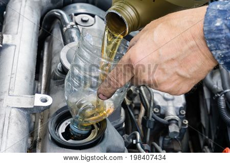 repairman is changing oil in car using old plastic bottle as a funnel