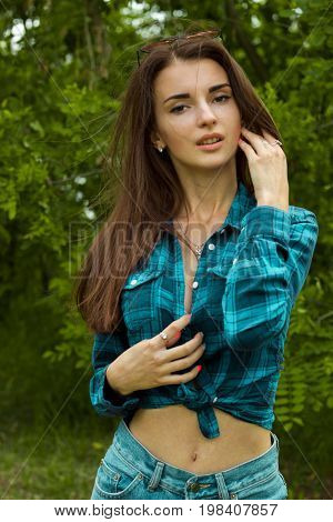vertical portrait of a beautiful young brunette in short Plaid Shirt