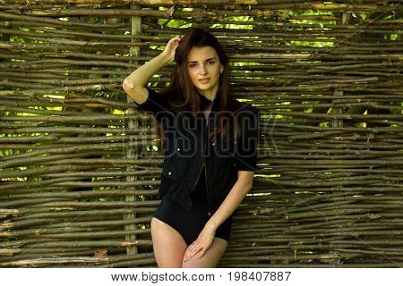 tender beautiful brunette in black suit stands near a wooden wall and stares into the camera