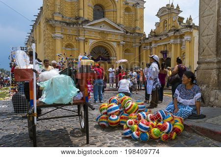 Antigua Guatemala - April 17 2014: Woman selling selling colorful rubber balls in a street of the old city of Antigua with the San Pedro Hospital on the background in Guatemala