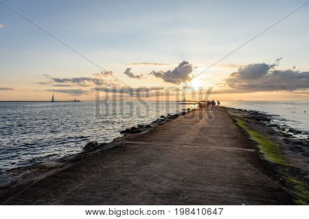 People Enjoying Sunset On The Breakwater In The Sea With Lighthouse