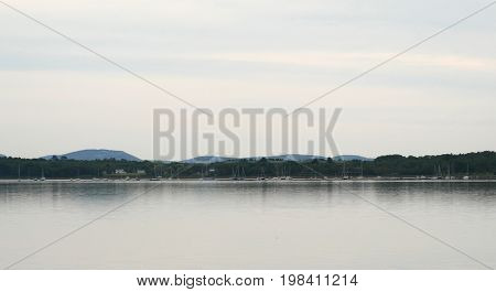 Stockton Springs harbor in Maine with moored sailboats and distant hills in the early morning light.