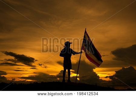 Boy scout stand holding Thai flag silhouette
