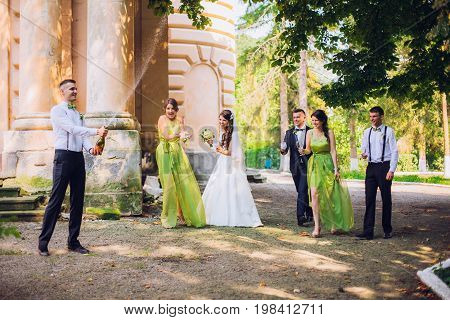 Stylish wedding couple, groomsman and bridesmaids with champagne explosion.