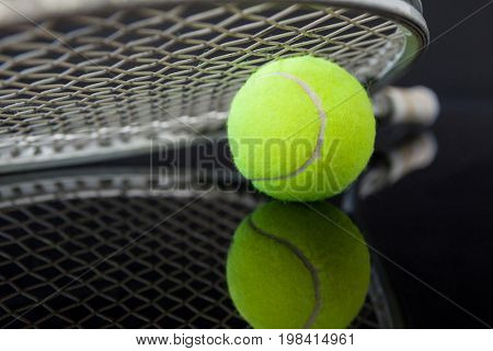Close up of tennis racket on ball with reflection against black background