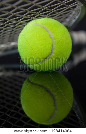 Close up of tennis racket on fluorescent yellow ball with reflection against black background