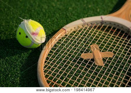 Close up of tennis ball and racket with bandage on field