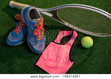 Sports shoes with tennis ball and racket by sports bra on field