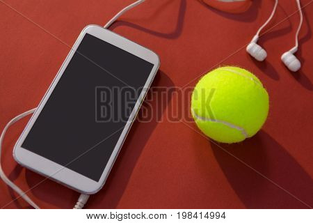 High angle view of tennis ball and mobile phone with in-ear headphones on maroon background