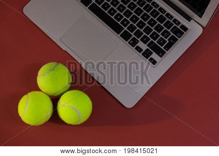 High angle view of tennis balls by laptop on maroon background