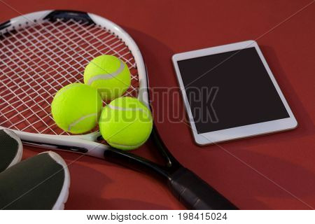 High angle view of sports shoes and digital tablet by balls on tennis racket over maroon background