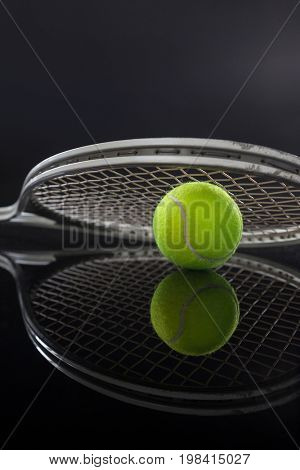Symmetrical view of tennis racket on ball with reflection against black background