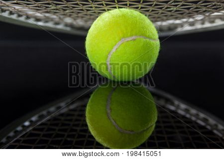 Close up of racket over tennis ball with reflection against black background