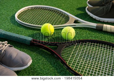 Close up of tennis rackets with balls and sports shoes on field