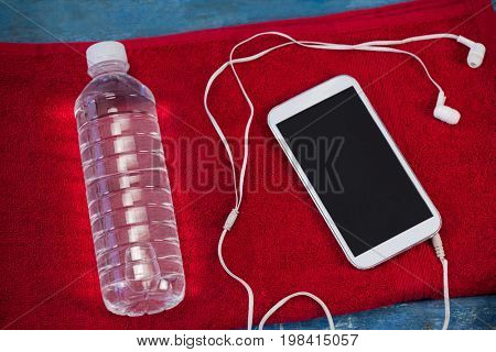 High angle view of water bottle and mobile phone with in-ear headphones on red napkin over table