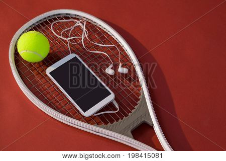 High angle view of mobile phone with in-ear headphones and ball on tennis racket over maroon background