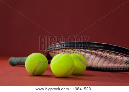 Close up of tennis racket on balls against maroon background