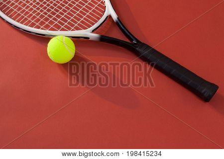High angle view of tennis racket and ball against maroon background