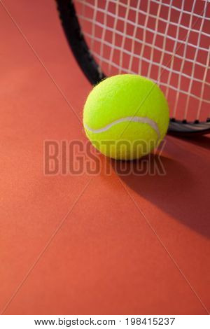 Close up of ball against tennis racket on maroon background