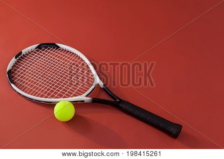 High angle view of tennis racket and fluorescent yellow ball against maroon background