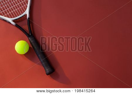 Overhead view of tennis racket and ball over maroon background