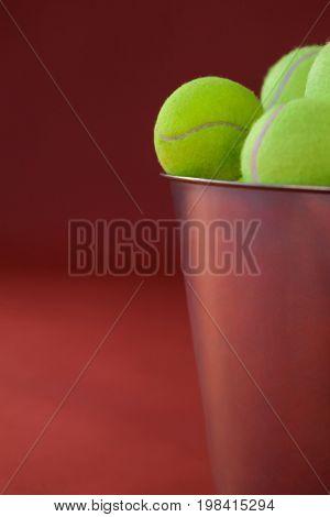 Close up of fluorescent yellow tennis balls in metallic bucket against maroon background