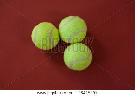 Overhead view of three tennis balls on maroon background