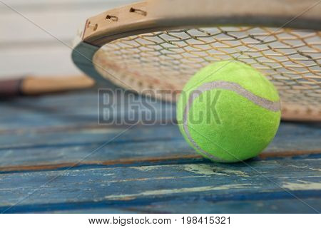 Close up of wooden tennis racket leaning on fluorescent yellow ball over blue table