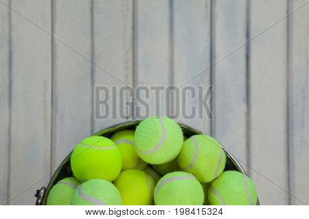 Directly above view of fluorescent yellow tennis balls in metallic bucket on white wooden table