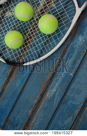 High angle view of fluorescent yellow balls on tennis racket over blue wooden table