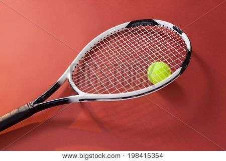 High angle view of fluorescent yellow ball with tennis racket on maroon background