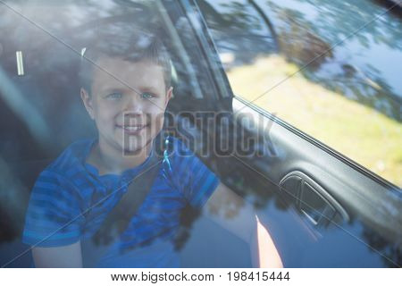 Portrait of teenage boy sitting in the front seat of car