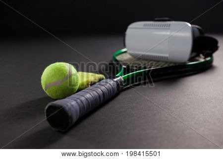 Close up of virtual reality simulator on tennis racket by ball against black background