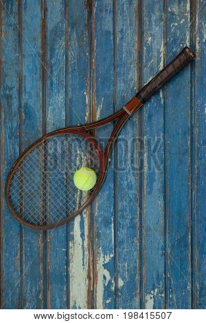 Overhead view of brown tennis racket with ball on blue wooden table