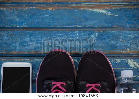 Overhead view of sports shoes amidst mobile phone and water bottle on blue wooden table