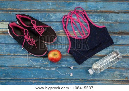 Overhead view of womenswear with apple and bottle by headphones on wooden table