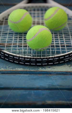 Close up of fluorescent yellow balls on tennis racket over blue wooden table