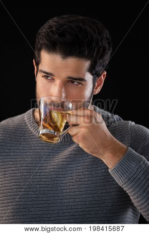 Thoughtful man having a cup of lemon tea against black background