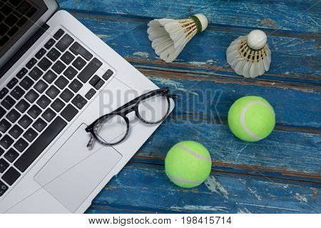 High angle view of laptop and eyeglasses with shuttlecocks by tennis balls on blue wooden table