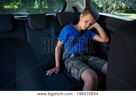 Teenage boy sleeping in the back seat of car