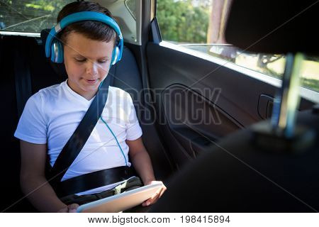 Attentive teenage boy using digital tablet in the back seat of car