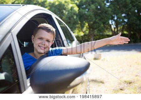 Portrait of teenage boy sitting in the back seat of car