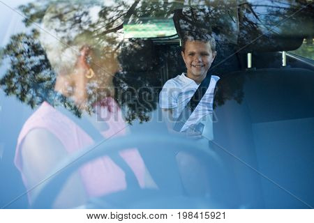 Grandmother driving a car while grandson sitting in the back seat of car