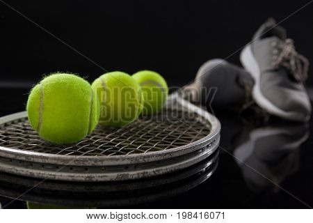 Close up of fluorescent yellow tennis balls on racket by sports shoes against black background