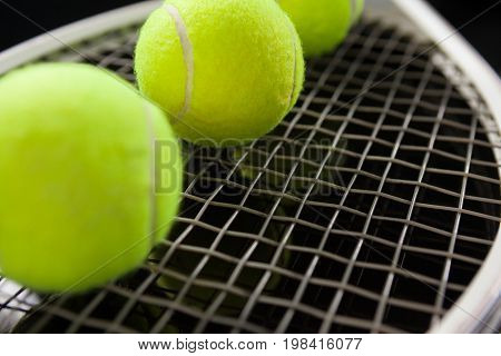 Close up of fluorescent yellow balls on tennis racket against black background