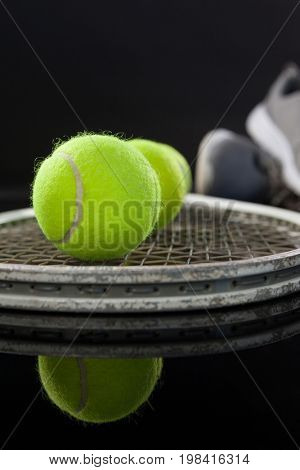 Close up of fluorescent yellow tennis balls on racket by sports shoes with reflection against black background