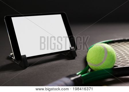 Close up of digital tablet by tennis racket and ball on black background