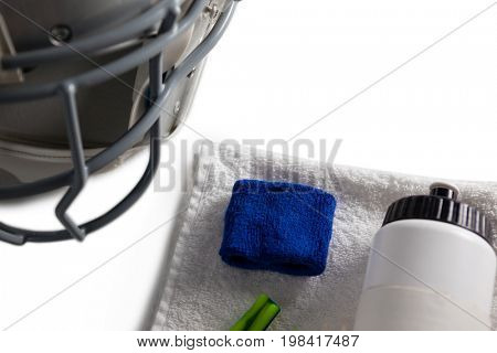 Close up of wristband and bottle on napkin by sports helmet
